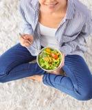 Mujer joven que come la ensalada fresca en casa Concepto sano del alimento imágenes de archivo libres de regalías