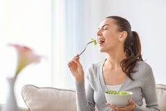 Mujer joven que come la ensalada fresca en casa Concepto sano del alimento fotos de archivo