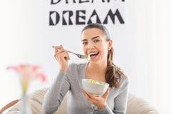 Mujer joven que come la ensalada fresca en casa Concepto sano del alimento foto de archivo