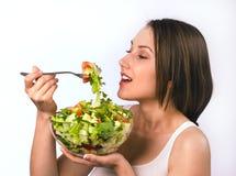Mujer joven que come la ensalada sana Foto de archivo