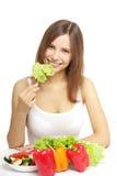 Mujer joven que come la ensalada sana en blanco Foto de archivo