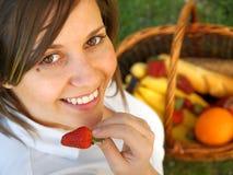 Mujer joven que come la fresa al aire libre Fotografía de archivo