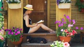 Mujer joven que come la fresa y que lee un libro almacen de metraje de vídeo
