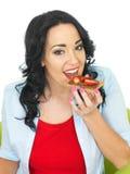 Mujer joven que come la galleta del trigo integral con la extensión del chocolate y las fresas cortadas frescas Imágenes de archivo libres de regalías