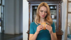Mujer joven que come la hamburguesa metrajes