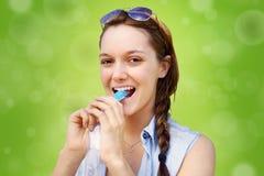 Mujer joven que come la invitación congelada Imágenes de archivo libres de regalías