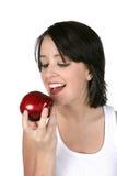 Mujer joven que come la manzana roja Foto de archivo libre de regalías