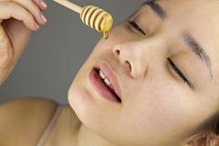 Mujer joven que come la miel Imagen de archivo libre de regalías