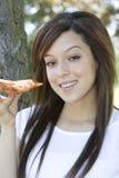 Mujer joven que come la pizza Foto de archivo libre de regalías