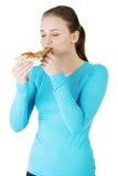 Mujer joven que come la pizza. Imagen de archivo