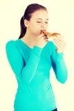 Mujer joven que come la pizza Fotos de archivo libres de regalías