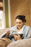 Mujer joven que come la sopa fotografía de archivo