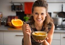 Mujer joven que come la sopa de la calabaza en cocina Foto de archivo libre de regalías
