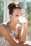 Mujer joven que come la taza de la mañana de café Imagenes de archivo