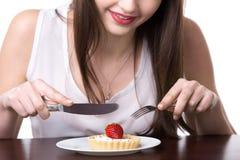 Mujer joven que come la torta Fotos de archivo