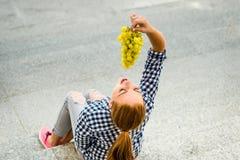 Mujer joven que come las uvas Foto de archivo