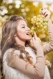 Mujer joven que come las uvas al aire libre Hembra rubia sensual que sonríe sosteniendo un manojo de uvas verdes Muchacha justa h Imagen de archivo