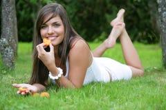 Mujer joven que come los albaricoques Fotos de archivo libres de regalías