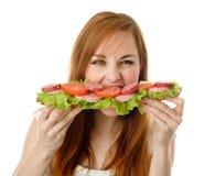 Mujer joven que come los alimentos de preparación rápida Foto de archivo libre de regalías