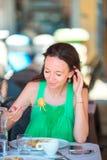 Mujer joven que come los espaguetis en el café al aire libre en vacaciones italianas Imagen de archivo