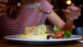Mujer joven que come salmones en restaurante metrajes