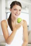 Mujer joven que come un Apple Fotos de archivo
