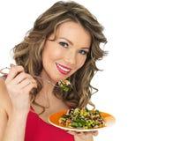 Mujer joven que come una ensalada asiática del estilo del arco iris aromático Imagenes de archivo