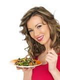 Mujer joven que come una ensalada asiática del estilo del arco iris aromático Foto de archivo