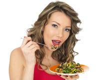 Mujer joven que come una ensalada asiática del estilo del arco iris aromático Fotografía de archivo libre de regalías