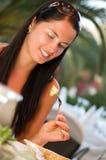 Mujer joven que come una ensalada en el restaurante fotos de archivo libres de regalías