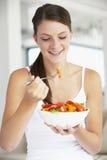 Mujer joven que come una ensalada sana Foto de archivo libre de regalías