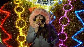 Mujer joven que come una hamburguesa al aire libre en un fondo de las luces de la Navidad almacen de metraje de vídeo