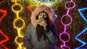 Mujer joven que come una hamburguesa al aire libre en un fondo de las luces de la Navidad almacen de video