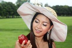 Mujer joven que come una manzana Imagen de archivo