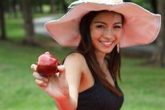 Mujer joven que come una manzana Foto de archivo libre de regalías