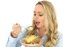 Mujer joven que come una patata cocida con queso Imagen de archivo