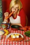 Mujer joven que come una zanahoria Fotos de archivo