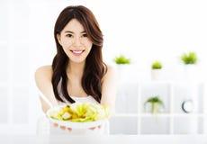 mujer joven que come y que muestra la comida sana Foto de archivo