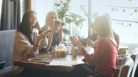 Mujer joven que comparte algo en su teléfono móvil con tres amigas de risa atractivas