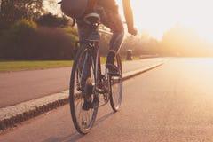 Mujer joven que completa un ciclo en el parque en la puesta del sol Fotos de archivo libres de regalías