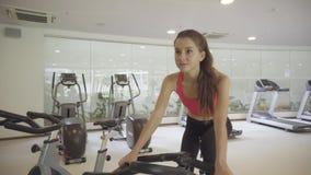 Mujer joven que completa un ciclo en la bicicleta estática en el gimnasio almacen de video