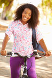 Mujer joven que completa un ciclo a lo largo de la calle para trabajar Imágenes de archivo libres de regalías