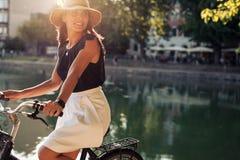 Mujer joven que completa un ciclo por una charca foto de archivo libre de regalías