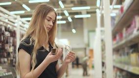 Mujer joven que compra el bulbo de la luz eléctrica almacen de metraje de vídeo