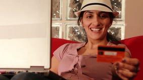 mujer joven que compra en línea con la tarjeta de crédito metrajes