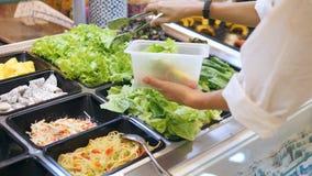 Mujer joven que compra verduras orgánicas en bufete de ensaladas en la tienda de alimentación El vegetariano se lleva la dieta de metrajes