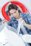 Mujer joven que comprueba el acondicionador de aire en casa fotografía de archivo libre de regalías