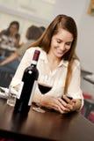 Mujer joven que comprueba su smartphone Imagen de archivo libre de regalías