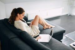 Mujer joven que comprueba sus correos electrónicos por mañana Imagen de archivo