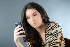 Mujer que comprueba sus mensajes de teléfono Fotos de archivo libres de regalías